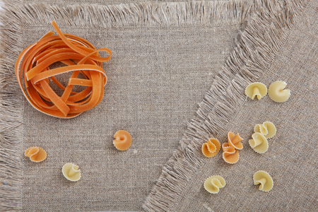 Pasta nest orange color on a napkin. View from above.