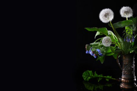 A bouquet of flowers from dandelions and blue and pink meadow flowers on a black background. A bouquet of wild flowers. A copy of space. A concept of still life. Stock Photo