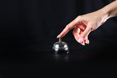 Female hand presses the call button staff call. Restaurant business or bar. Copy space. Photo on a black background. Visitor service concept. 스톡 콘텐츠