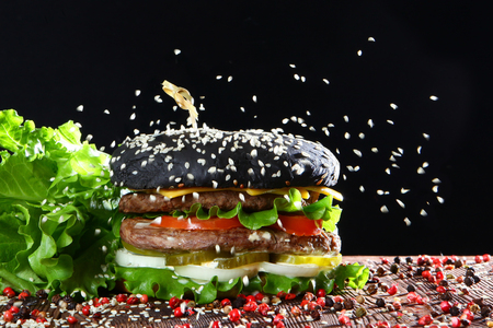 Black burger with two cutlets on a black background. On the burger pours sesame. Fast food concept.