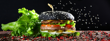 Black burger with two cutlets on a black background. On the burger pours sesame. Fast food concept. Side view banner