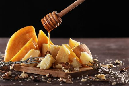 A drop of honey falls into pieces of cheese. Still life concept. Photo on a dark background. Illustration to the text.