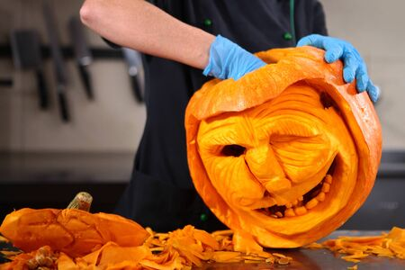 A woman carves a scary face out of a pumpkin. Pumpkin carving. All Saints Day. Autumn holiday. Photo without a face.
