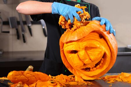 A scary face carved from a pumpkin. Holiday Halloween. Macro photo. Photo without a face. Zdjęcie Seryjne