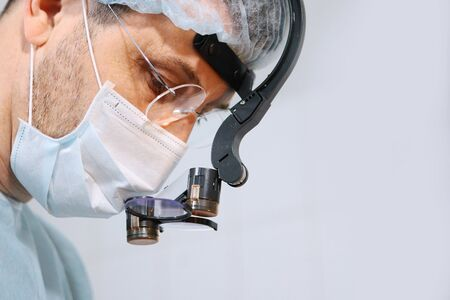 Close-up of a dentist surgeons face with a microscope in glasses. Binocular glasses. Copy space. 스톡 콘텐츠