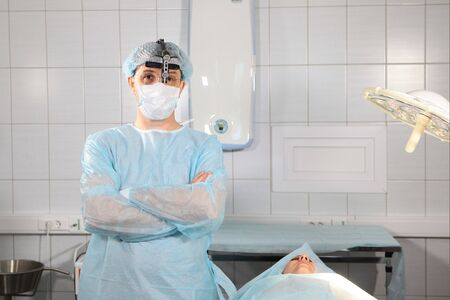 Dentist surgeon in the operating room with binocular glasses. Doctor and patient at the dental clinic before surgery. 스톡 콘텐츠