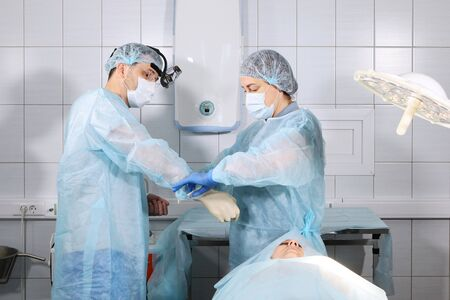 A nurse helps to put on gloves to a doctor surgeon before surgery. Health and beauty concept. Photo in the operating room. Macro photo. 免版税图像