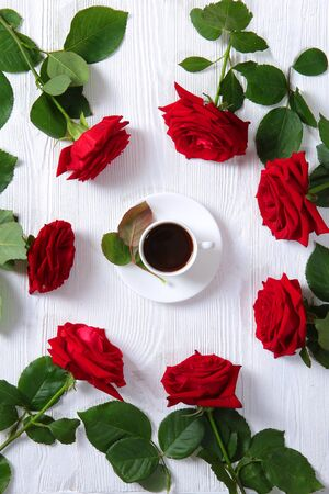 Red roses and a cup of coffee on a white background. Morning drink concept.