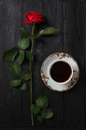 Red rose and a big cup with coffee on a black background. Morning drink concept.