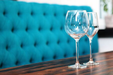 Two empty wine glasses on a table in a restaurant against a blue sofa. Macro photo. Photo in the interior.Copy space
