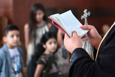 The hands of a priest in an Armenian church hold a book and a cross. The text and faces of the children are out of focus. Photo without a face in the interior. Concept of religion and service to God.