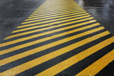 Yellow-black signal strip at the factory. Floor painting for worker safety. Allocation of hazardous areas. Safety in a factory or factory. Macro photo.