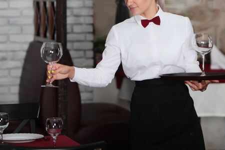Girl waitress serves glasses for wine. Photo without a face in the interior of the restaurant. The concept of service in the restaurant business.