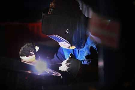 Welder In a protective helmet at the workplace. Photo without a face. The concept of professions with a risk to life.