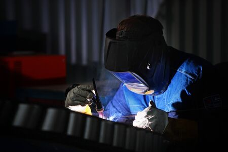 Work welder close-up on the production. Photo without face with copy space. The concept of professions with a risk to life. Photo in the interior.