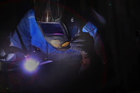 A worker by profession, a welder, closeups the details of a bearing in production. Photo without a face. The concept of professions with a risk to life. Photo in the interior. Archivio Fotografico