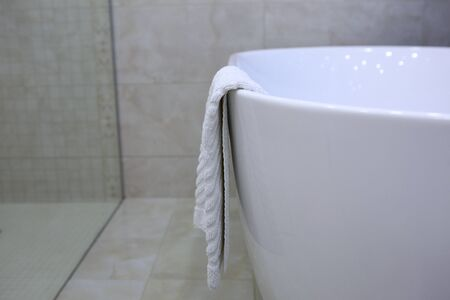 A white terry towel for the feet hangs on the edge of the bathtub. Photo in the interior of the bathroom. Copy space. View from above. Hotel business concept.