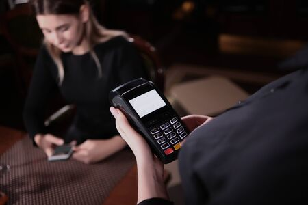 The waitresss hands hold the terminal for payment. Close-up photo. The view from the top. The guest sits at the table with the phone out of focus. Zdjęcie Seryjne
