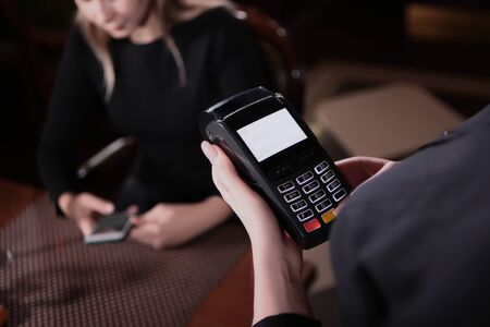 Payment by Bank transfer through the terminal in the restaurant.Photos without a face. The guest at the table is out of focus. Zdjęcie Seryjne