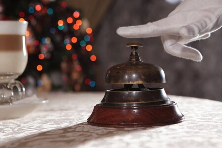 Antique bell for calling the waiter. White-gloved hand. The concept of service in the restaurant business. Macro photo in the interior.Copy space. Only hand