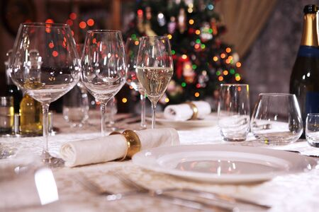A glass of champagne, half filled, stands on a beautifully laid table.The concept of the celebration. The Christmas tree is out of focus. Flank. Copy space. Macro photography in the interior. Imagens
