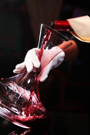 Red wine pours from the bottle into the decanter. Macro photo. Copy space. The enrichment of the wine with oxygen. Photos without a face.