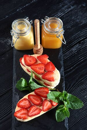 Soft halloumi cheese with mint. Natural product. The view from the top. Strawberries lie on top of the cheese. Honey in jars. Copy space. 免版税图像