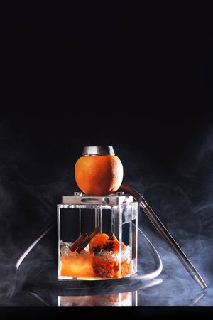 A square flask for a hookah based on sea buckthorn and orange. A transparent flask of a hookah. Concept of smoking and unhealthy habits.