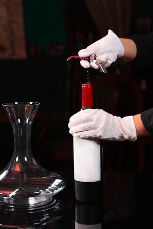 The white-gloved hands of a waiter open a bottle of red wine with a corkscrew. Photo on a dark background in the interior of the restaurant. Copy space.Photo without face, only hands