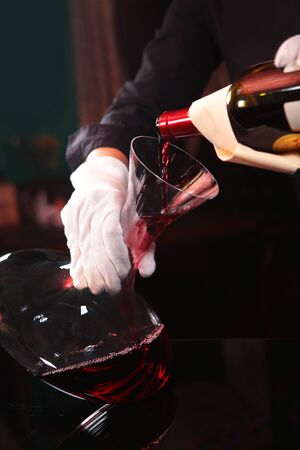 Red wine is poured into the decanter. enrichment of wine with oxygen. Photo without a face in the interior of the restaurant. Only hand.