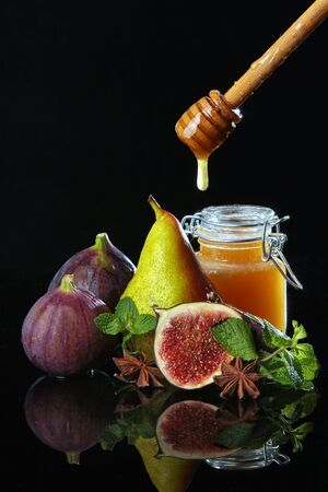 Jar with honey and fruits on a black background. Copy space. Still life concept.Macro photo.