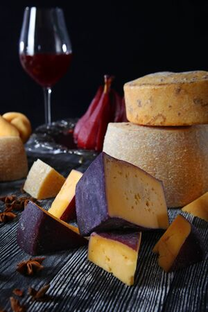 An assortment of hard craft cheeses on a wooden board and on a black background. Cheese production in small volumes.