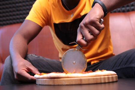 Close-up of a black young man's hands cutting pizza into pieces. Unrecognizable photo with no face, only hands. Copy of the space.