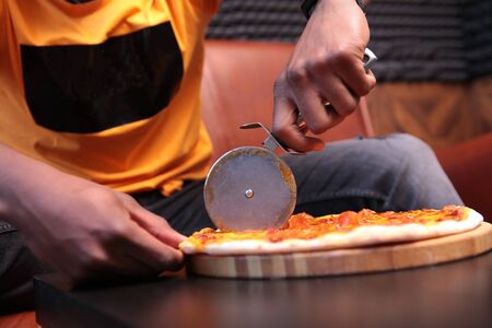 Close-up of a black young man's hands cutting pizza into pieces. Unrecognizable photo. Copy space.