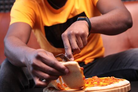 A young African-American man was cutting up a pizza. An unrecognizable photo of the interior. Copy space. Stok Fotoğraf