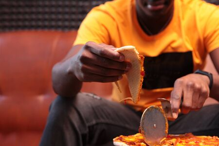A young African-American man was cutting up a pizza. Knife for pizza in hand. Unrecognizable photo in the interior. Copy space. Stok Fotoğraf