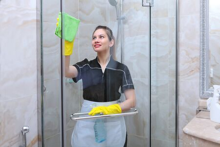 A girl in a uniform washes the transparent doors in the shower stall. Napkin and spray in hand.The bathroom is decorated with marble tiles. The concept of cleanliness and hygiene. Copy space.