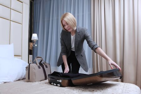 A businesswoman unpacks her suitcase in a hotel room. Business trip or business trip. Copy space.