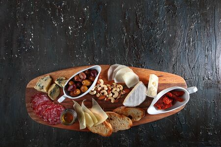 Cheese and cold cuts with nuts on a wooden Board. Textured aged dark background. Top view. Copy space.