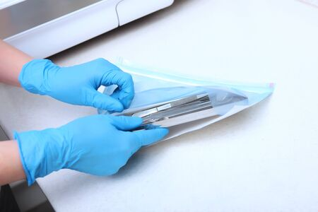 The hands of a medical worker in blue gloves pack dental devices for sterilization. Unrecognizable photo. Only hand. Copy space.