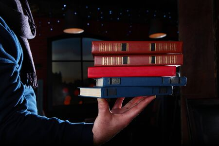 Books in a man's hand. Unrecognizable photo. Different volumes of books. Photo on a black background. Copy space.