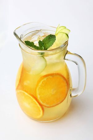 Lemonade of oranges and apples with mint in a tall glass jug on a white background. Top view. Copy space.