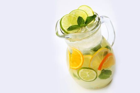 Orange and lime lemonade with mint in a tall glass jug on a white background. An isolated object. Top view. Copy space.