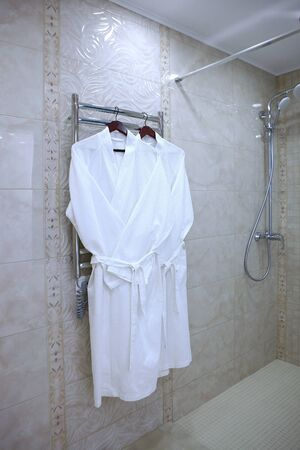 Two white cotton dressing gowns hang in the bathroom. Vertical photo in the interior without people. Copy space.