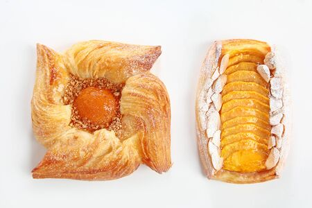 Danish puff with apricot jam or Danish rolls with peach on a white background. An isolated object. Copy space. Top view. Zdjęcie Seryjne