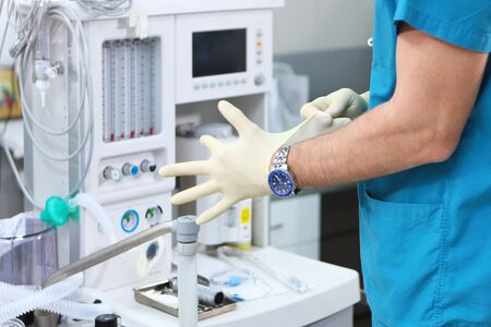 The doctor puts on gloves against the background of a ventilator. Unrecognizable photo. Copy space. Banque d'images
