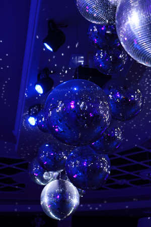 Disco ball with bright rays, night party with blue background. Party dance hall celebration at night club with lots of flashy colors. Rotating disco mirror ball.Vertical photo.