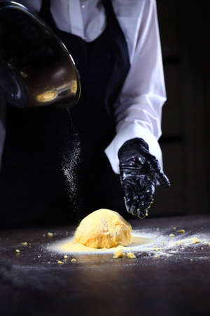 A cook wearing protective gloves kneads cornmeal dough. Gluten-free product.Egg is broken into corn flour. Dough for cooking different dishes. Healthy food. Unrecognizable person.Vertical photo.