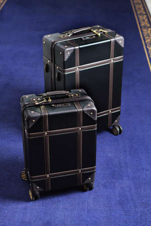Two suitcases with luggage are on the carpet in the hotel. Comfortable modern luggage. Vertical photo. Blue carpet. Top view. Free space.