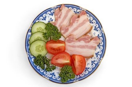 Slices of bacon with slices of cucumbers, tomatoes and sprigs of green parsley on porcelain plate on a white background photo